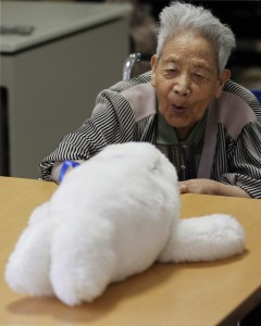Long-term care resident plays with Paro, the robot seal