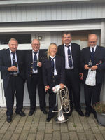 Picture of Dr. Jønsson posing with a brass instrument and four older, white men.